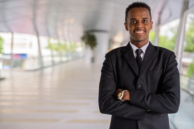 Portrait of successful young african businessman smiling outdoors with arms crossed