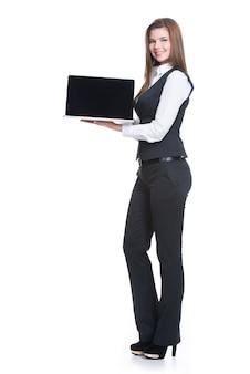 Портрет успешной молодой бизнес-леди держа компьтер-книжку в полную длину - изолированный на белизне.
