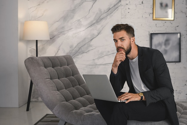 Portrait of successful young unshaven businessman in elegant formal jacket working remotely on laptop, using free wireless internet connection in luxurious hotel suite while being on business trip