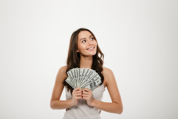 Portrait of successful young woman with long hair holding lots of money cash, smiling on camera over white wall