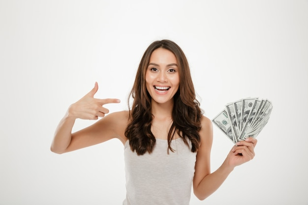 Portrait of successful young woman with long hair showing lots of money cash, smiling on camera over white wall