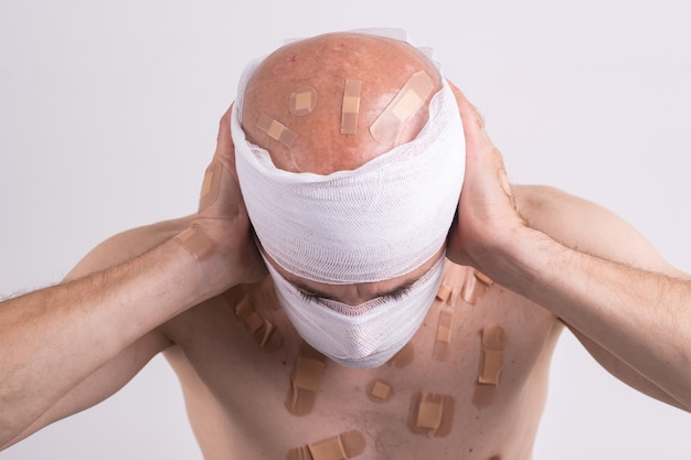 Portrait of sufferer male with bandaged head feeling bad and covers his hands on ears.