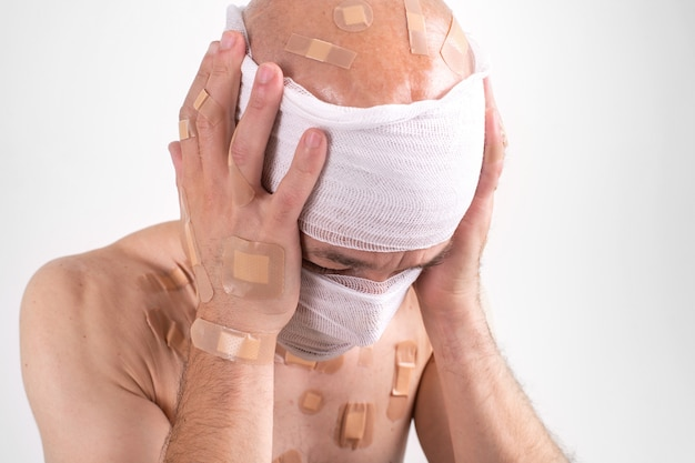 Portrait of suffering male with bandaged head feeling bad and covers his hands on ears