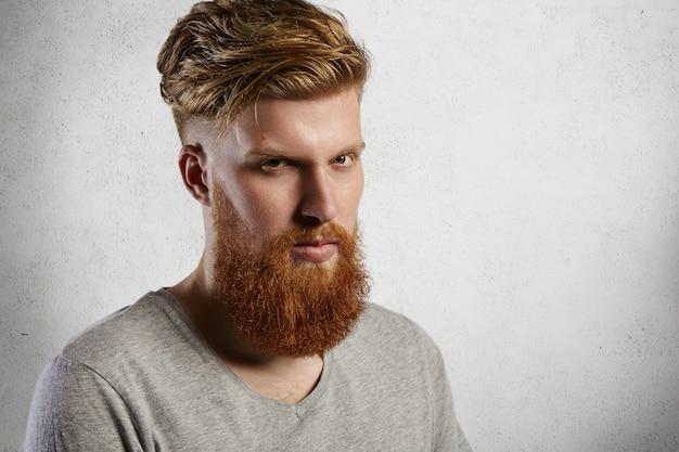 Ritratto di uomo arrabbiato imbronciato con barba sfocata hipster vestito casualmente con espressione del viso serio e severo, dimostrando la sua mascolinità.