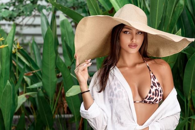 Portrait of a sultry beautiful brunette in a leopard bikini and a big straw hat