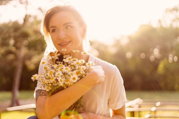 Ritratto di una donna solare che abbraccia un mazzo di camomilla con i raggi del sole sul viso godendosi la vita