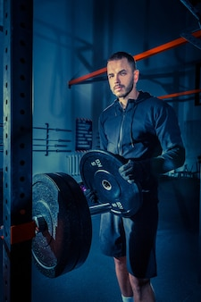 Portrait of super fit muscular young man working out in gym with barbell