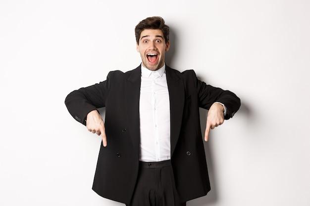 Ritratto di un uomo super felice che mostra l'offerta promozionale di natale, puntando le dita verso il basso e sorridendo stupito, indossando un abito formale da festa, in piedi su sfondo bianco