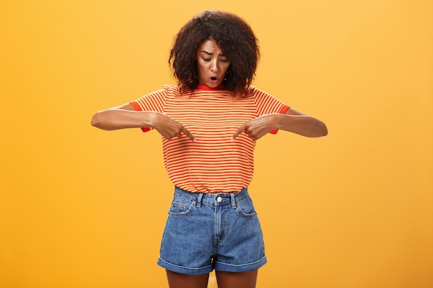 Portrait of a surprised african american female with curly hairstyle looking and pointing at stomach over orange wall