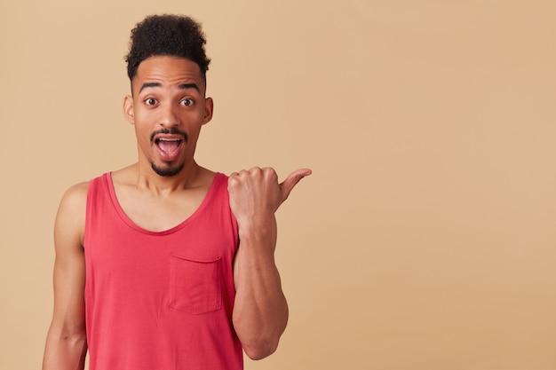 Ritratto del maschio afroamericano sorpreso con l'acconciatura afro. indossare canottiera rossa. indicando con il pollice a destra nello spazio della copia, isolato su un muro beige pastello