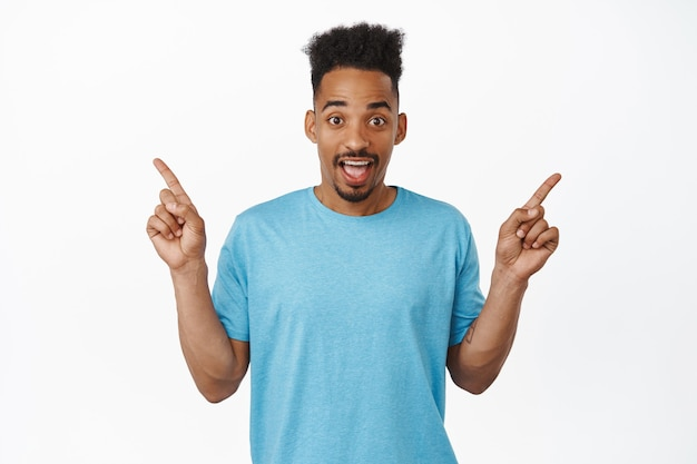 Portrait of surprised african american man pointing fingers sideways, showing left and right products, two sale discounts, standing in blue t-shirt on white.