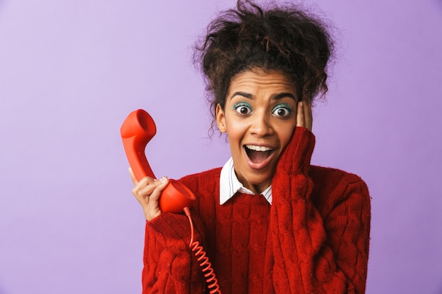 Portrait of surprised african american woman with afro hairstyle screaming while holding red handset, isolated