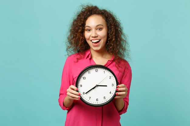 Portrait of surprised african girl in pink casual clothes holding round clock isolated on blue turquoise wall background in studio. people sincere emotions, lifestyle concept. mock up copy space.
