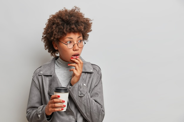 Portrait of surprised afro american woman gazes shocked aside drinks takeaway coffee wears round spectacles fashionable jacket isolated over grey wall