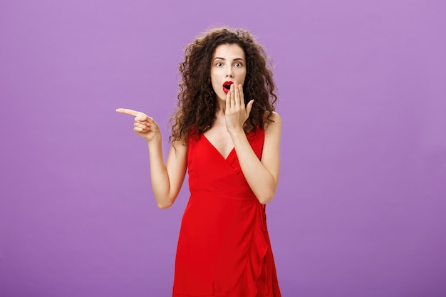 Portrait of surprised and amazed charming elegant lady with evening make-up in red dress covering opened mouth from shock and amazement pointing left curious and questioned over purple background.