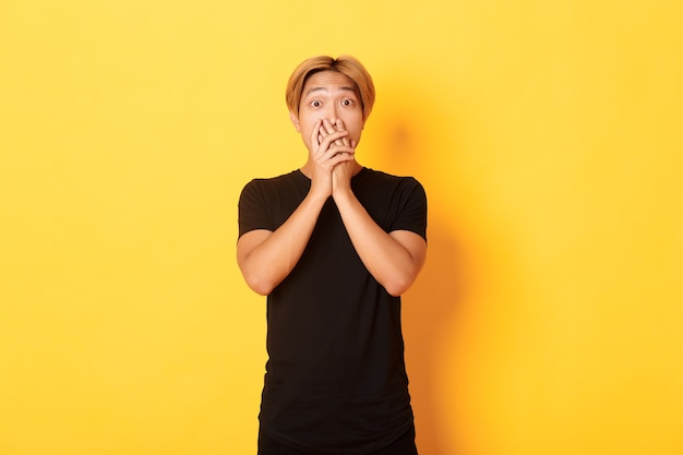 Portrait of surprised asian handsome guy with blond hair