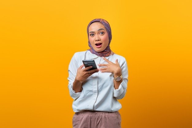 Portrait of surprised asian woman using mobile phone with open mouth over yellow background