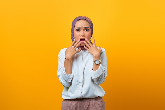 Portrait of surprised asian woman with open mouth over yellow background