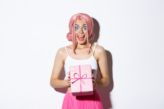 Ritratto di ragazza attraente sorpresa che sembra eccitata, riceve un regalo per il compleanno, indossa una parrucca rosa, in piedi.
