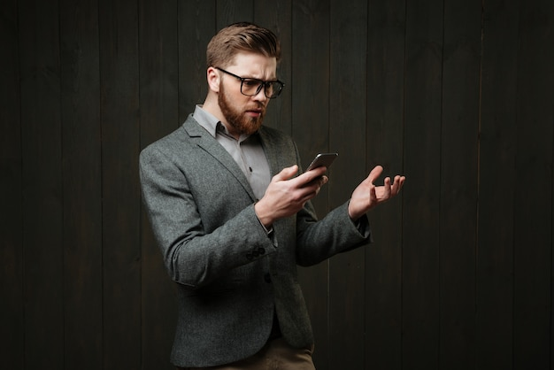 Portrait of a surprised bearded man in eyeglasses and casual suit holding mobile phone isolated on the black wooden background