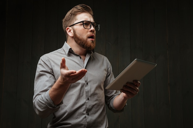 Portrait of a surprised bearded man in eyeglasses holding tablet computer and gesturing isolated on a black wooden surface