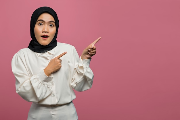 Portrait of surprised beautiful asian woman pointing with finger to empty space