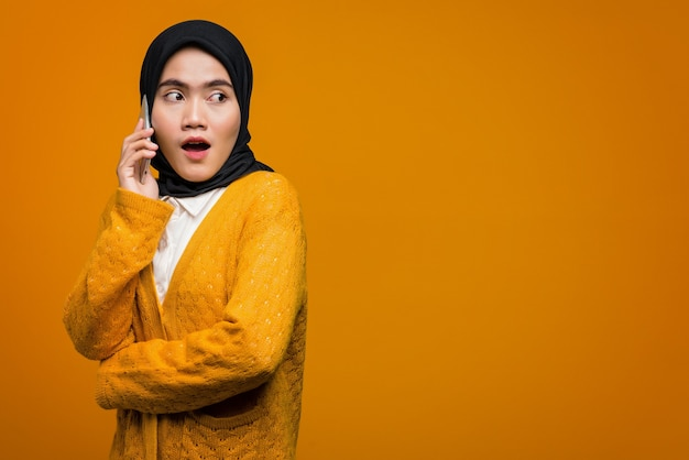 Portrait of surprised beautiful asian woman talking with a friend on mobile phone
