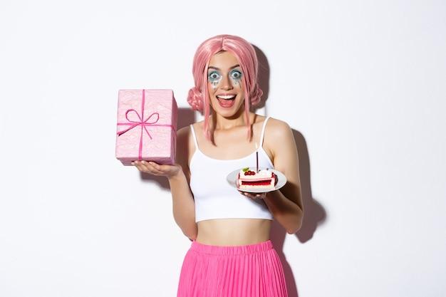 Ritratto di bella ragazza sorpresa in parrucca rosa, ricevere il regalo di compleanno, tenendo la torta del b-day e sorridendo felice, in piedi.