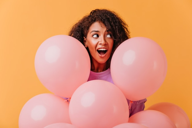Portrait of surprised birthday girl looking away while posing with balloons. funny african lady fooling around during party.