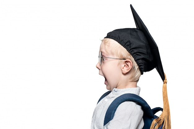 Portrait of a surprised blond boy in glasses, an academic hat and a schoolbag