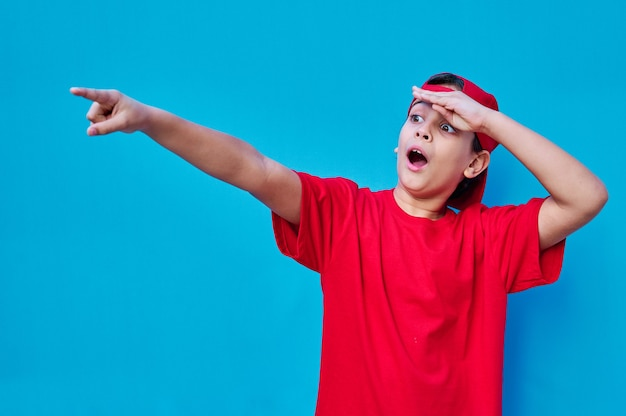 A portrait of surprised boy in red cap and t-shirt points with finger. copy space ...