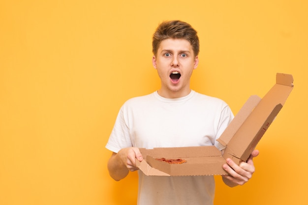 Portrait of a surprised boy with a box of pizza in his hands