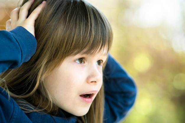 Portrait of surprised child girl holding hands to her head outdoors in summer.