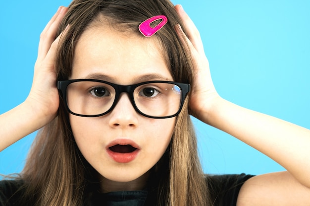 Portrait of surprised child girl wearing looking glasses holding hands to her face isolated on blue wall