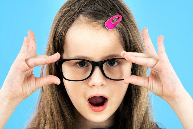 Portrait of surprised child girl wearing looking glasses holding hands to her face