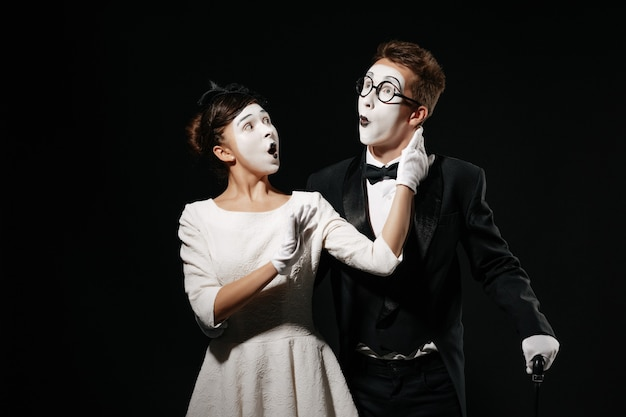 Portrait of surprised couple mime on black background. man in tuxedo and glasses and woman in white dress