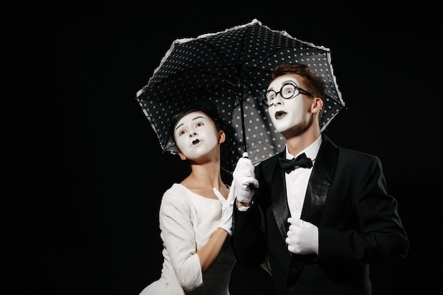 Portrait of surprised couple mime with umbrella on black background. man in tuxedo and glasses and woman in white dress