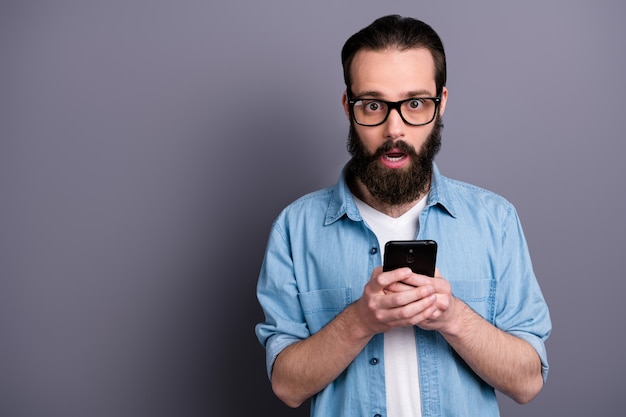 Portrait of surprised crazy guy use smartphone get sale discount notification stare stupor scream wow omg unbelievable wear casual style clothes  isolated over grey color wall