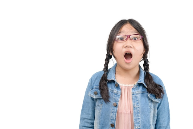 Portrait of surprised cute little asian girl child standing isolated over white background. looking at camera and open mouth, emotion face concept