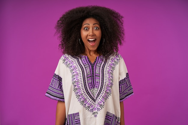 Ritratto di donna dalla pelle scura sorpresa in abiti casual in posa sul viola, mantenendo le mani lungo il corpo, sollevando le sopracciglia e con gli occhi spalancati