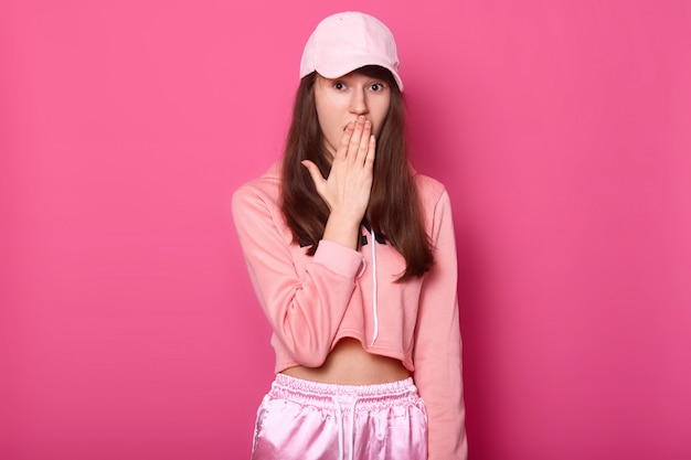 Portrait of surprised european brunette teenager covers her opened mouth with hand, dressed in stylish rose sweatpants, hoodie and cap, stands against pink studio wall. people and emotions concept.