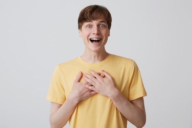 Il ritratto del giovane eccitato sorpreso con la bocca aperta indossa la maglietta gialla