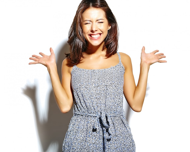 Portrait of surprised fashion woman in casual hipster summer clothes with no makeup making  on white wall