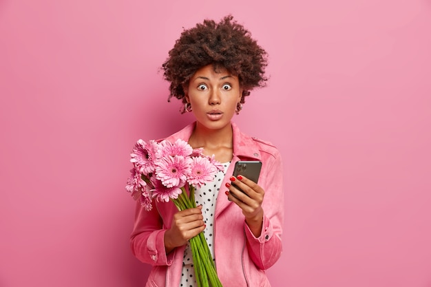 Portrait of surprised female model holds bouquet of flowers modern smartphone receives unexpected congratulation on birthday dressed in stylish clothes
