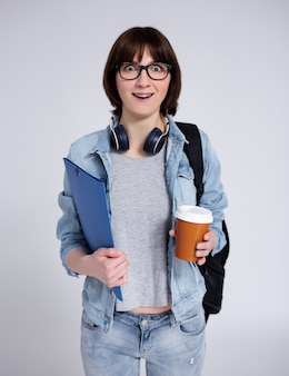 Portrait of surprised female student in eyeglasses with backpack, folder and cup of coffee over gray background
