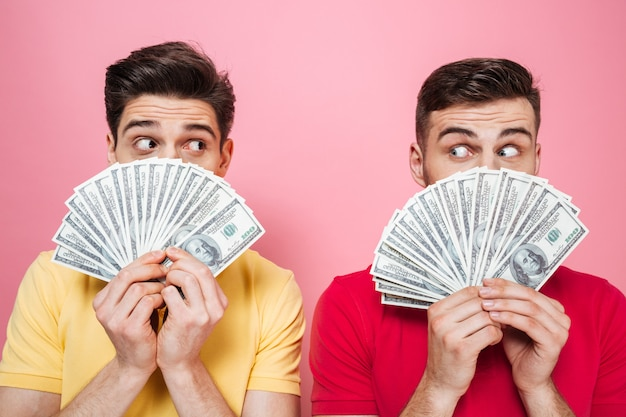 Portrait of a surprised friends holding money