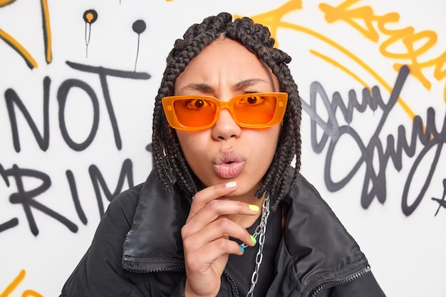 Portrait of surprised funky female teenager keeps hand on chin looks with wondered expression at camera wears orange sunglasses black jacket poses against painted graffiti wall