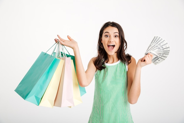 Portrait of a surprised girl in dress holding shopping bags