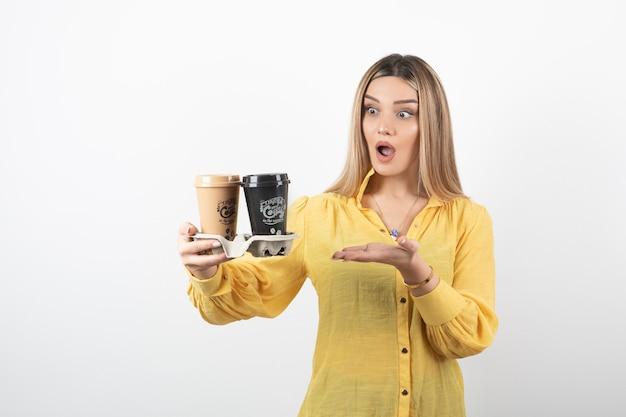 Ritratto della ragazza sorpresa che tiene le tazze di caffè e che sta sul bianco.
