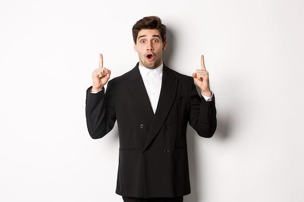 Ritratto di un bell'uomo d'affari sorpreso in abito nero, dicendo wow e guardando stupito, puntando le dita verso lo spazio della copia, in piedi su sfondo bianco
